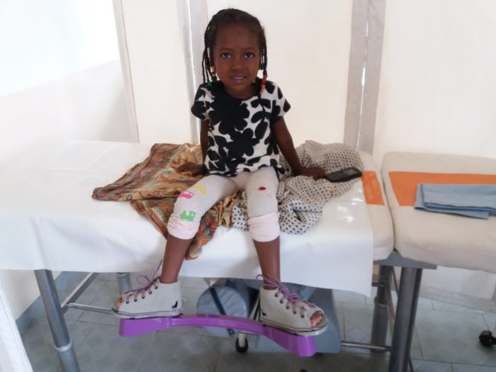 Assane sits on the clinic table wearing the MiracleFeet brace