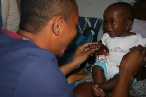 Andri with smiling baby in the clinic