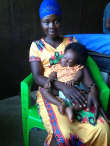 Sleeping child with bare feet free of clubfoot sits on her mother's lap. Mother is wearing a yellow patterned dress and blue head wrap.