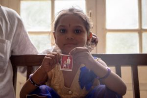 close up photo of bhumika holding photo of herself with untreated clubfoot