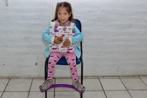 smiling girl holding a book sits in chair. she is wearing the purple MiracleFeet brace.