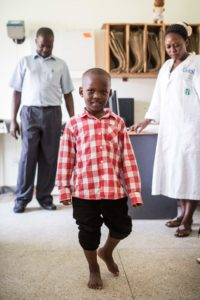 smiling boy with pants legs rolled up to show his corrected feet. he is walking towards the camera while medical providers look on in the background.