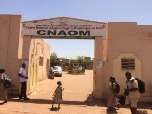 Child stands outside looking up at CNAOM sign in Bamako Mali