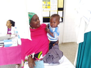 Obed's grandmother holds him during a clinic visit