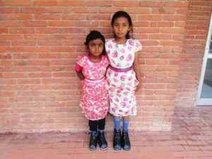 two girls wearing orthotics, standing side by side in front of a brick wall