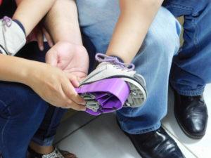 parent slides shoe into purple MiracleFeet brace on child's foot