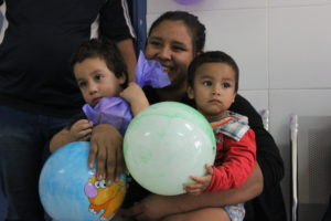 younger brothers sit on mothers lap holding balloons during world clubfoot day celebration